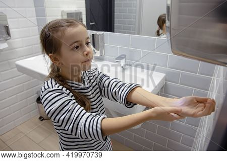 Funny Little Girl Dries Her Hands In The Bathroom. Hygiene And Cleanliness In A Coronavirus Environm