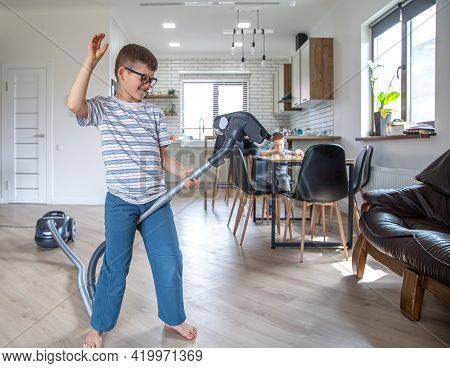 A Little Boy With Glasses Is Having Fun And Cleaning The House With A Vacuum Cleaner.