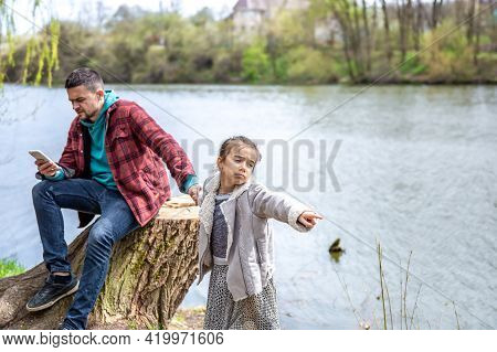 The Little Girl Pulls Dad Out For A Walk, But He Checks His Phone And Pays No Attention.
