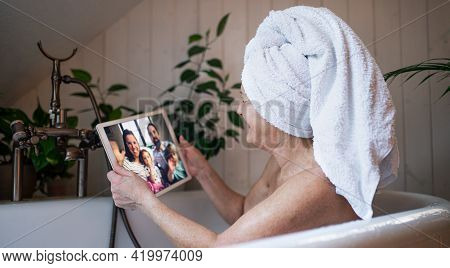 Senior Woman With Tablet In Bath Tub At Home, Video Call With Daughter And Grandchildren.