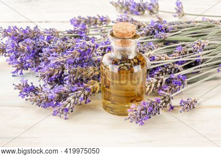 Lavender Essential Oil With A Bouquet Of Flowers, Toned Image