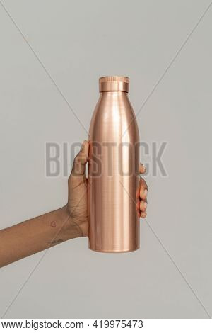 Hand holding a copper stainless steel bottle