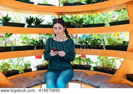 A Cute Girl Sitting On A Bench In A Spherical Gazebo With Plants. A Relaxation Area With Free Wi-fi.