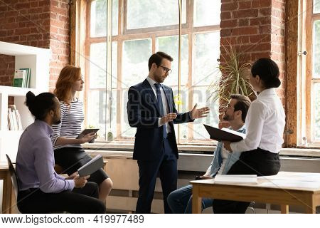 Diverse Colleagues Employees Listening To Mentor Coach At Meeting