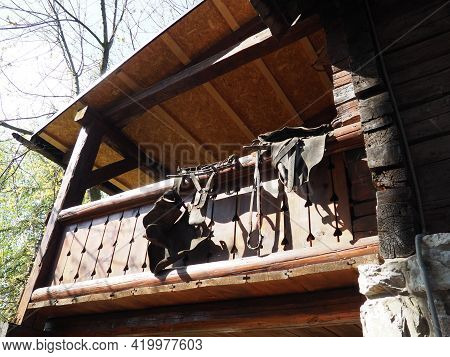 A Leather Saddle, Bridle And Stirrups Hang From The Railing Of The Log House Terrace. Stanisici, Bij
