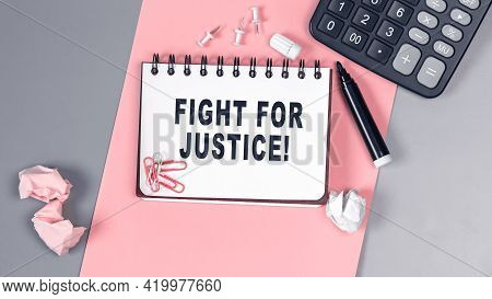 The Words Fight For Justice Written On A White Notebook. Closeup Of A Personal Agenda. Top View. Off