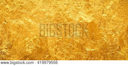 Shiny gold background made of rough textured gold leaf.