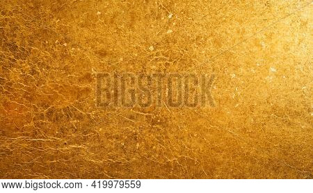 Shiny gold background made of rough textured gold paper.