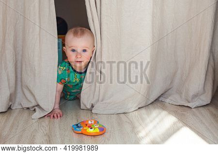 Eight-nine Month Baby Boy Playing Hide And Seek Behind The Curtains