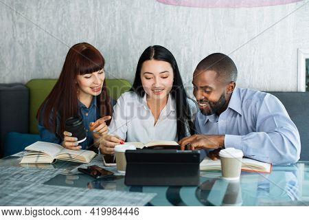 Multi-ethnic Group Of Three Young People Working Together At Cafe Or Coworking. Smiling Friends Stud
