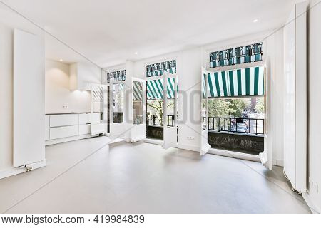 Interior Of Spacious Light Room With Doors Opened To Balcony With Canopy On Sunny Summer Day