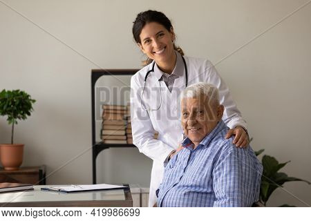 Portrait Of Smiling Doc And Retired Patient In Doctor Office