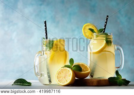 Summer Fresh Drink With Lemons And Mint Leaves On Blue Background. Lemonade In Jar With Straw.