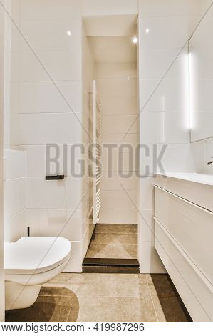 Flush Toilet And Sink With Mirror Located Near Narrow Passage In Contemporary Bathroom With White Ti