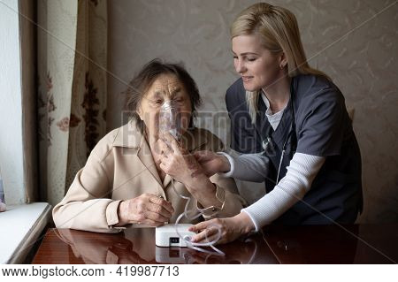 Kind Young Female Nurse Caring For A Very Old Female Patient, Hospital