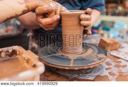 Male Potter Works At A Table With Clay Doing Ceramics