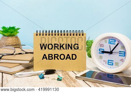 A Sign With The Inscription Working Abroad On The Table With Office Supplies