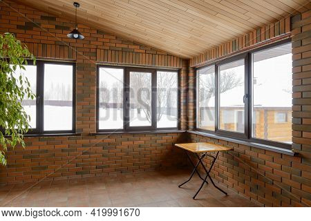 Interior Of The Brick Veranda With Large Windows, Table And Lamp