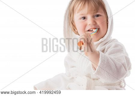 Little Baby Brushing His Teeth Under A White Towel