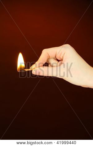 Burning match in female hand, on dark brown background