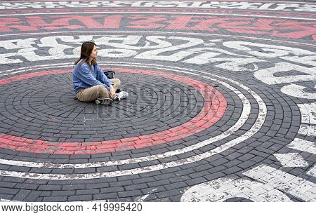 Young Woman In Blue Sweatshirt Alone Sitting On Street Cobbled Square In The Form Of Circles And Dre