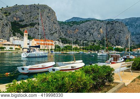 Fishing And Sailing Boats On The Cetina River In Omis Resort. Anchored Boats And High Mountains In B
