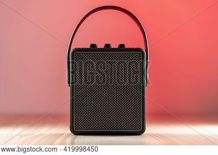 Black Bluetooth Loudspeaker On A Reddish Background