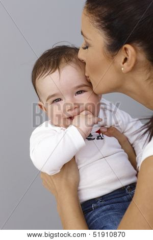 Mother kissing baby boy affectionately. Baby smiling with thumb in mouth.