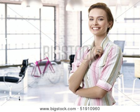 Casual female officeworker at office, smiling.