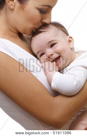 Closeup portrait of young mother embracing baby boy, kissing his head. Baby smiling.