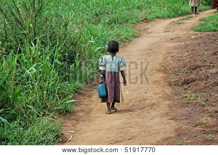 GULU UGANDA AFRICA - CIRCA MAY 2005: Unidentified little girl carries a blue jerry-can down a dirt path circa May 2005 in Uganda Africa. poster
