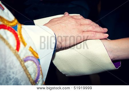 Catholic Priest Holding His Hand On Newlyweds' Hands Coverred In Stole