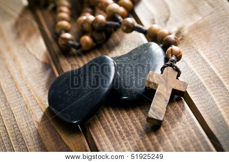 stone hearts with rosary beads on wooden background