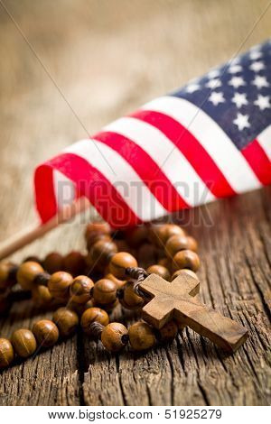 rosary beads with american flag on wooden background