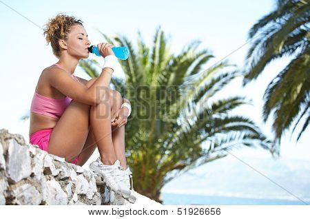 Fitness brunette drinking water and cooling off after running at the tropical beach