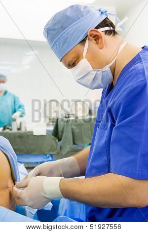 Doctor anesthesiologist performing epidural anesthesia in the operating room poster