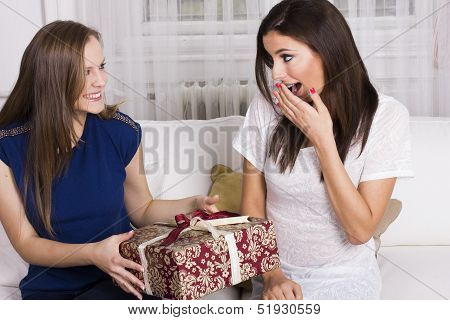 Two happy women with present