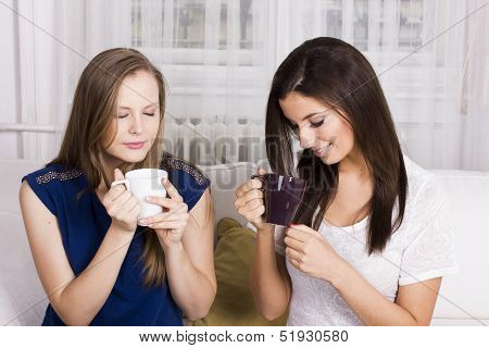 Two beautiful girlfriends with coffee on the bed