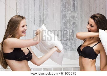 Two sexy girls having pillow fight in the bedroom