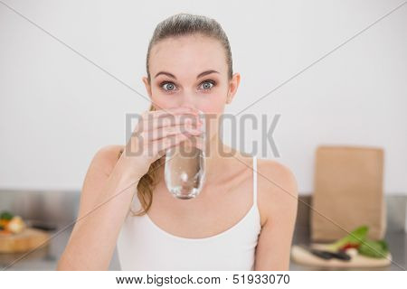 Happy young woman drinking glass of water in the kitchen at home
