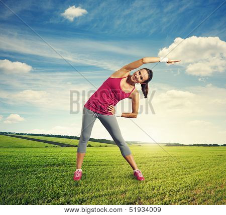 cheerful young woman doing warm-up at outdoor