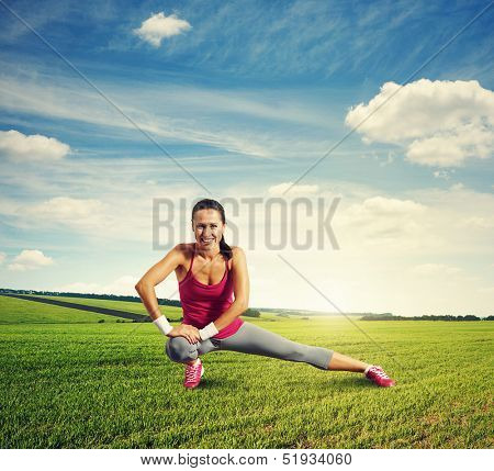 cheerful sportswoman doing warm-up at outdoor