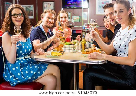 Friends or couples eating fast food and drinking beer and wine in a American fast food diner