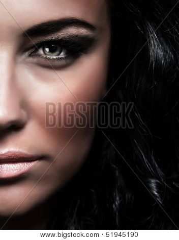 Closeup portrait of gorgeous glamorous woman, half of face, stylish makeup, fashion lifestyle, black glossy hair, desire and passion concept