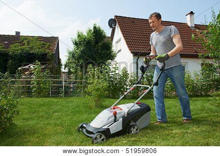 man cutting grass in his garden yard with lawn mower