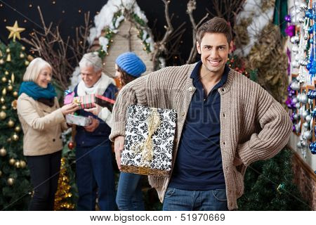 Portrait of happy young woman holding Christmas present with family standing in background at store