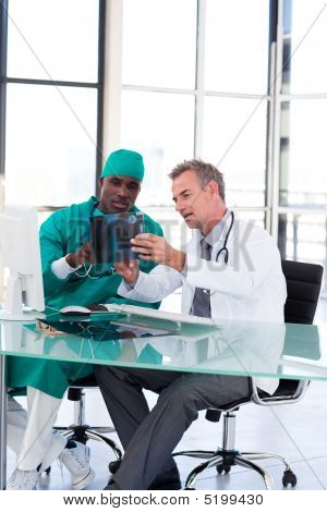 Doctor And Surgeon Studying An X-ray