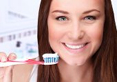 Closeup portrait of attractive female clean teeth in the bathroom, dental clinic, dentistry health care, healthy lifestyle, tooth whitening concept poster