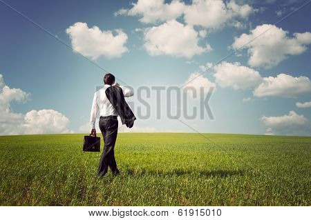 Businessman In A Suit Walking On A Spacious Green Field With A Blue Sky
