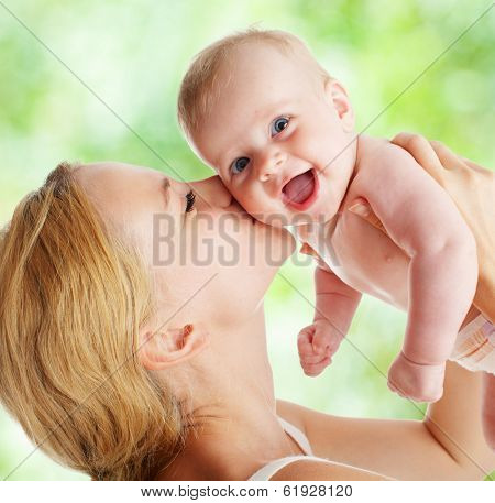 Mother with baby outdoors. Happy family with newborn in summer